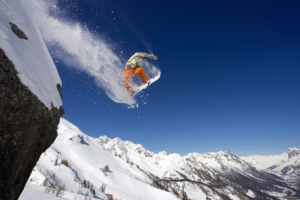 Male snowboarder jumps from rock on mountainside. Serre Chevalier France