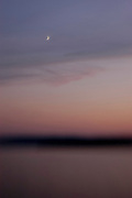 A crescent moon rises as the sunset fades over Lake Superior near Bayfield, Wis., on Aug. 9, 2005. The photograph was made using a selective-focus lens while aboard the Madeline Island Ferry.