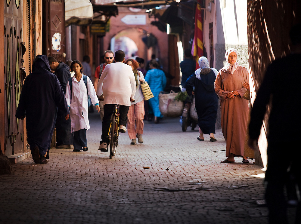 A cyclist weaves his way through tourists and vendors in Marrakech's narrow alleys