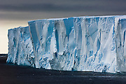 The sheer face of a tabular iceberg looms beneath overcast skies, South Orkney Islands, Scotia Sea, South Atlantic Ocean