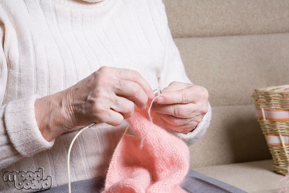 Elderly woman sits knitting