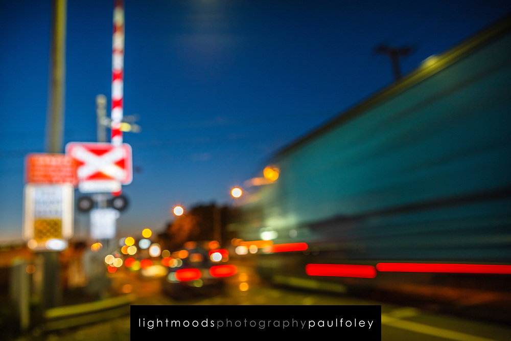 Blurred car and truck passing through a railway level crossing in Sydney, Australia