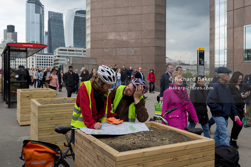 A man looks adoringly at a woman cyclist while looking at a map of the capital, as commuters cross London Bridge during the evening rush-hour, from the City southwards to Southwark, on 3rd May, in London, England