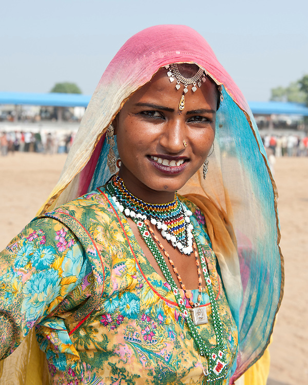 Portrait of a young Indian woman, beautifully dressed in colourful traditional sari with beaded necklaces, nose piercing and headress.