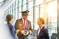 Portrait of Mature pilot talking to flight attendants in airport with yellow lens flare