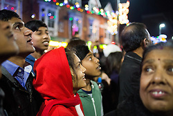"""© Licensed to London News Pictures. 01/11/2015. Leicester, UK. More than 35,000 people were estimated to have attended the annual Diwali ight switch-on which took place along the named """"Golden Mile"""" in Belgrave Road, Leicester. Pictured, part of the crowd watch as the lights come on. Photo credit : Dave Warren/LNP"""