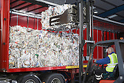 Man in vehicle loading stacks of recycled paper on to lorry
