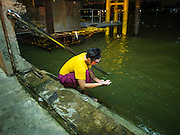 "26 NOVEMBER 2014 - BANGKOK, THAILAND: A performer washes his hands in the Chao Phraya River before a Chinese opera performance at the Chow Su Kong Shrine in the Talat Noi neighborhood of Bangkok. Chinese opera was once very popular in Thailand, where it is called ""Ngiew."" It is usually performed in the Teochew language. Millions of Chinese emigrated to Thailand (then Siam) in the 18th and 19th centuries and brought their culture with them. Recently the popularity of ngiew has faded as people turn to performances of opera on DVD or movies. There are about 30 Chinese opera troupes left in Bangkok and its environs. They are especially busy during Chinese New Year and Chinese holidays when they travel from Chinese temple to Chinese temple performing on stages they put up in streets near the temple, sometimes sleeping on hammocks they sling under their stage.      PHOTO BY JACK KURTZ"