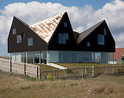 Sunshine shining on metal roof of modern house on the seafront at Thorpeness, Suffolk, England