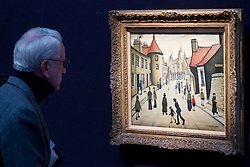 "© Licensed to London News Pictures. 21/03/2014. London, UK. A visitor to Sotheby's auction house views ""Street Musicians"" (1938) (est. GB£600,000-800,000) by British artist LS Lowry during the press view for a new sale of the artist's work in London today (21/03/2014). The auction, entitled ""Lowry: The AJ Thompson Collection"", features works by Lowry assembled over a 30 year period by collector A.J. Thompson. Photo credit: Matt Cetti-Roberts/LNP"