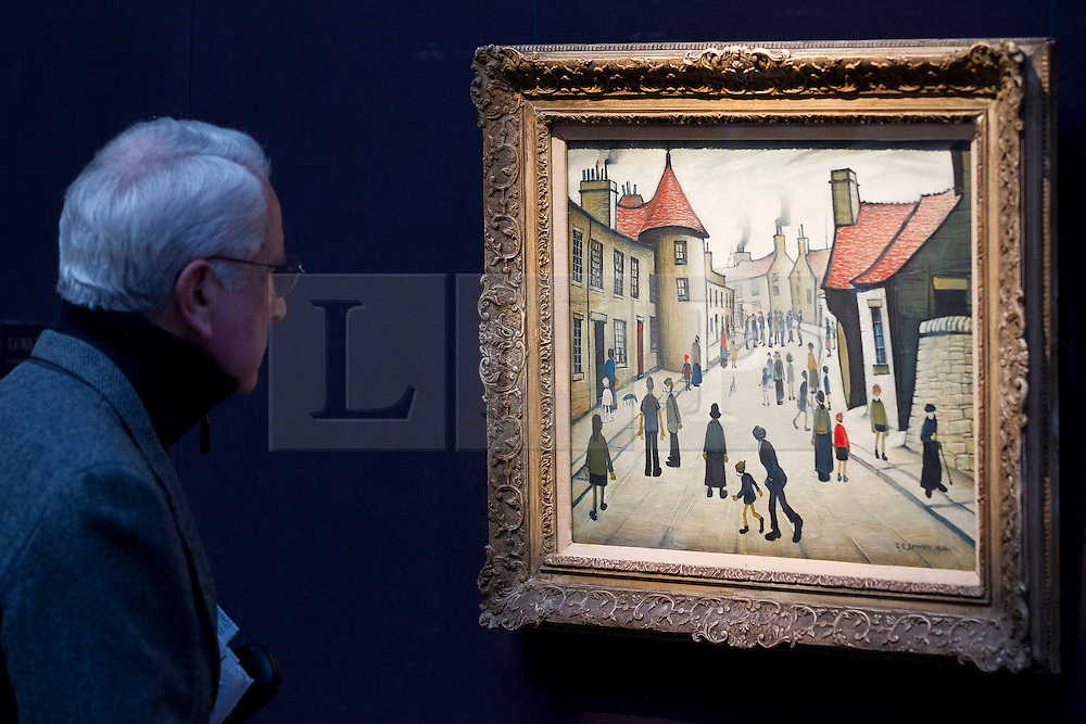 """© Licensed to London News Pictures. 21/03/2014. London, UK. A visitor to Sotheby's auction house views """"Street Musicians"""" (1938) (est. GB£600,000-800,000) by British artist LS Lowry during the press view for a new sale of the artist's work in London today (21/03/2014). The auction, entitled """"Lowry: The AJ Thompson Collection"""", features works by Lowry assembled over a 30 year period by collector A.J. Thompson. Photo credit: Matt Cetti-Roberts/LNP"""