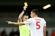 Referee Tom Neild shows a yellow card to Ross Sykes of Accrington   during the EFL Sky Bet League 1 match between Rochdale and Accrington Stanley at the Crown Oil Arena, Rochdale, England on 12 October 2019.