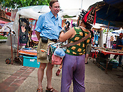 """26 JUNE 2011 - CHIANG MAI, THAILAND:  An Akha woman tries to sell a foreign tourist a souvenir at the """"Walking Street"""" market in Chiang Mai, Thailand. The Walking Street market is a weekly, Sunday night, market along Ratchadamnoen Street in Chiang Mai. The Akha are one of the ethnic minority hill tribes that live in northern Thailand.     PHOTO BY JACK KURTZ"""