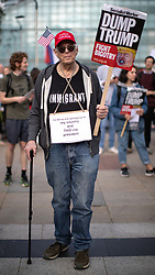 """© Licensed to London News Pictures . 03/06/2019. Manchester, UK. An American man wearing an """" IMMIGRANT """" t-shirt in the crowd . A Manchester Together Against Trump demonstration in Cathedral Gardens , central Manchester , during the first day of US President Donald Trump's visit to the UK . Photo credit: Joel Goodman/LNP"""