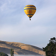 Ballooning over the Hawkes Bay region of the North Island of New Zealand. as the mist sits in the valley at dawn. The flights provide pristine views and spectacular scenery of the surrounding wine region and mountain background at dawn. Early Morning Balloons operates out of Hastings and is run by owners Andrew and Sally Livingston, Rosser Road, Hastings. Hawkes Bay. New Zealand. 12th January 2010 Photo Tim Clayton.