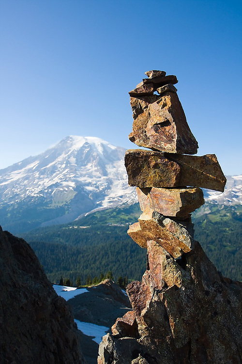 Mount Rainier and a rock cairn, as seen from below Pinnacle Peak in the Tatoosh Range, Mount Rainier National Park, Washington.