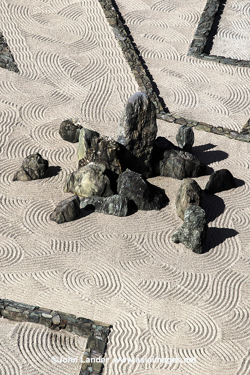 "Hachijin-no-Niwa Garden at Kishiwada Castle - this very unique karesansui garden is set in the courtyard of Kishiwada-jo and designed to be viewed from the windows of the castle. It is a very modern design of geometric, linear stones punctuated by groups of rocks in a field of pebbles. The garden was designed by Mirei Shigemori, a leading figure in the development of the modern Japanese garden. The garden was completed in 1953. Eight groups of rocks represent the ""Battle Formation of the Eight Positions"". Each of these eight groupings has a name: heaven, earth, bird/phoenix, dragon, cloud, serpent, tiger or wind.  The garden challenges our thinking about the usually calm effects of stone gardens. Based on the layout of a mythological battle conducted by Chinese General Zhuge Liang, the stone setting at the center of the design, named Central Camp, is the garden's focal point.  Eight stone sub-camps:  Heaven, Earth, Wind, Cloud, Dragon, Tiger, Phoenix and Snake surround the main encampment."