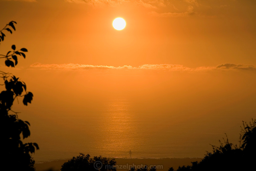 Pacific Ocean sunset with sailboat shot from Kona Palisades Estates, Big Island, Hawaii.