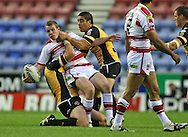 Wigan - Sunday 20th September 2009:Cameron Phelps of the Wigan Warriors is tackled by Rangi Chase of the Castleford Tigers  during the Engage Super League Elimination Playoff match between The Wigan Warriors & The Castleford Tigers at the DW Stadium in Wigan. (Pic by Steven Price/Focus Images)