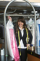 Woman holding up clothes in the laundrette