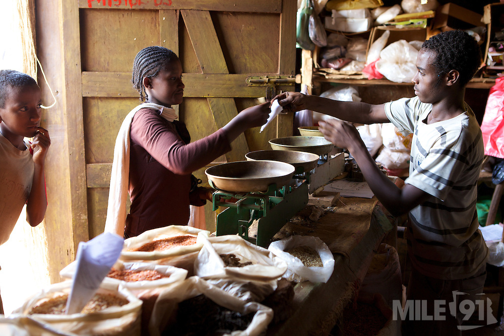 A woman buying a very small quantity of lentils in the market in Finote Selam, Ethiopia.