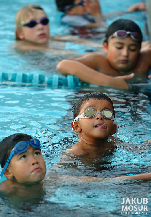 From top to bottom Daniel Bittman, 13, Pete Stathakos, 12, Rayniero Machado, 9 with tongue sticking out, and Erik Sap, 6, take swimming instructions at a Oakland Undercurrents swim class, a swim program for inner-city kids..Event on 11/2/05 in Oakland...JAKUB MOSUR / The Chronicle
