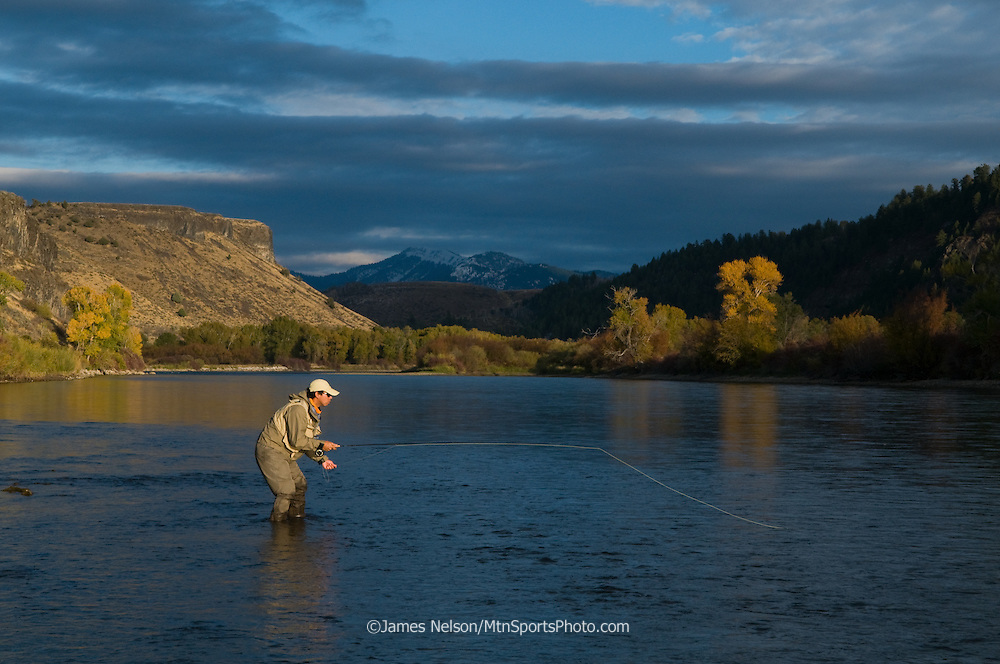 An angler fly fishes for trout during an autumn day on the South Fork of the Snake River, Idaho.