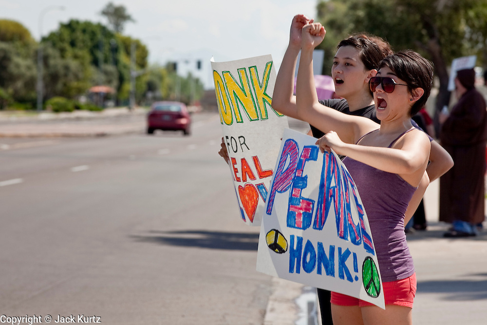 """Sept. 6, 2009 -- TEMPE, AZ: GABRIELLA MARVIN, from Phoenix, AZ, and her friends picket and encourage motorists to honk in front of the Faithful Word Baptist Church in Tempe, AZ, Sunday. Steven Anderson, the minister at the Faithful Word Baptist Church, an independent fundamentalist Baptist church, in Tempe has repeatedly said he hoped US President Barack Obama would die from a brain tumor and Sunday, Sept. 6, reiterated that he """"hates"""" President Obama. More than 200 people from a variety of liberal and progressive churches in the Phoenix area picketed Anderson's church Sunday morning, outnumbering his small congregation of about 50.  Photo by Jack Kurtz"""
