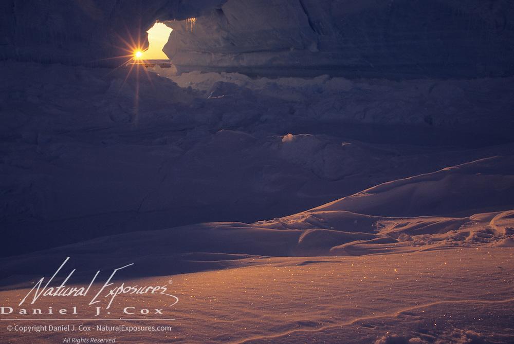 Evening light shines through a hole in a tabular iceberg. Atka Bay, Antarctica
