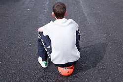 Back view of young boy alone; with no friends to play football with,