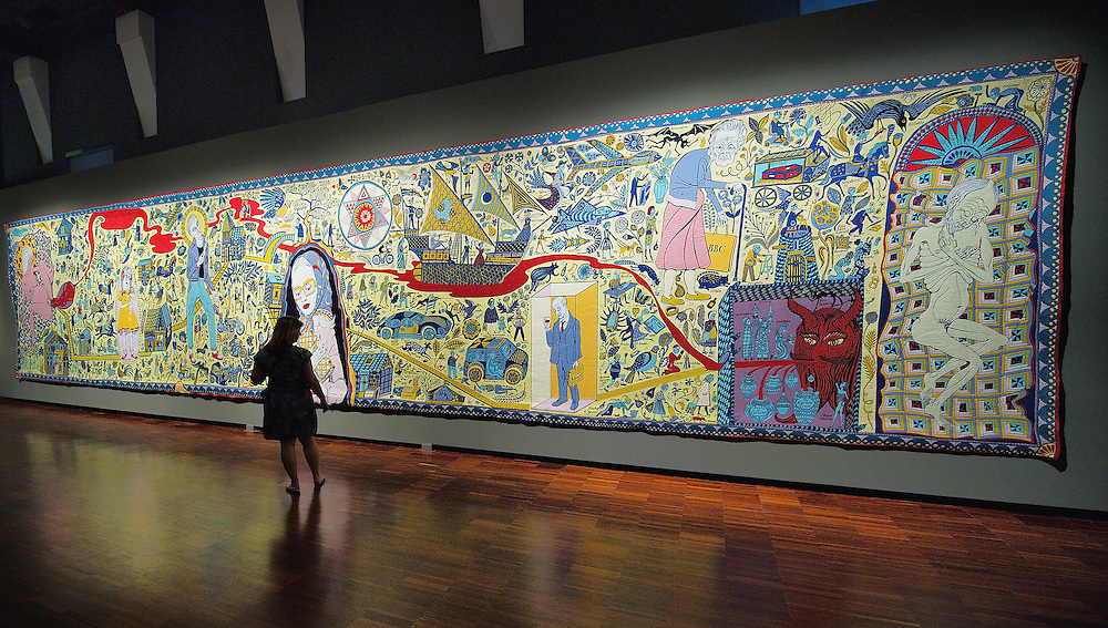 "VENICE, ITALY - JUNE 16: A woman admires ""The Wolthamstow Tapestry 2009"" a 15mt long tapestry by Grayson Perry on June 16, 2011 in Venice, Italy.Penelope's Labour: Weaving Words and Images, is an exhibition of antique and contemporary tapestries and carpets, curated by Adam Lowe and Jerry Brotton and will stay open until September 18."
