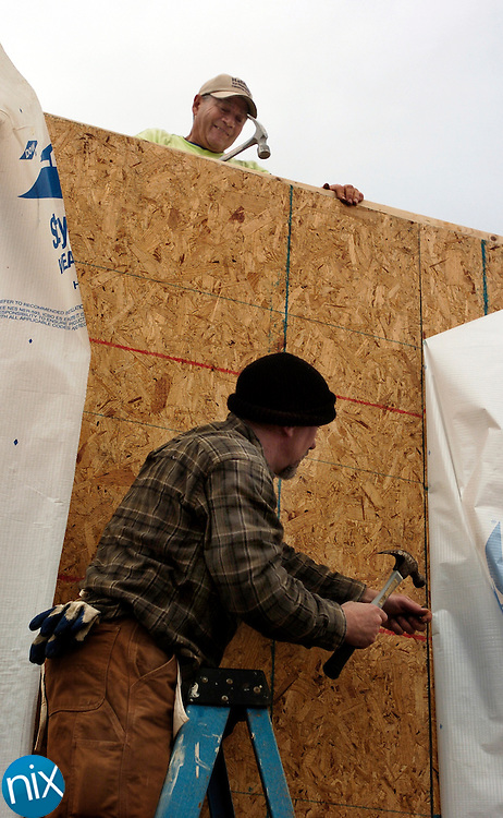Brad Fisher, top, and Todd Monroe install an outside wall on a Habitat for Humanity house in Magnolia Crossing in Concord Saturday morning.