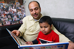 Single parent and son reading a book together on the sofa at home,