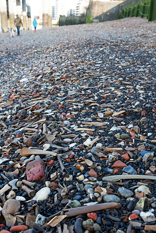 Old animal bones, brick, and coal fragments washed up along the Thames, London, UK.