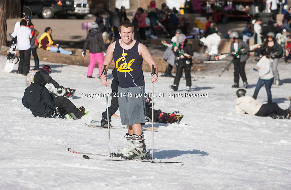 A man wears short clothes snowboarding at Mountain High resort in Wrightwood , California Friday January 3, 2014. Warm temperatures hit Southern California, which stand in stark contrast to record snowfall in the east. According National Weather Service, a record high temperature of 68 degrees was set at Sandberg, California today. This tied the old record of 68 set in 2012.  (Photo by Ringo Chiu/PHOTOFORMULA.com)