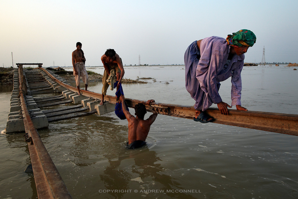 Men cross a broken railway line near Shikarpur, in Sindh Province, Pakistan.