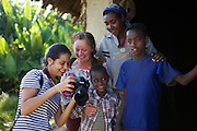 Ginny showing photographs to people outside a hut in Ethiopia.