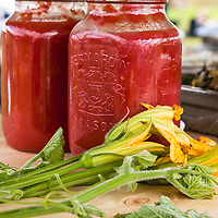 Jars of red tomato sauce on a wood table with squash blossoms in front.