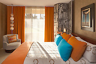 Colorful modern bedroom lit dramatically by window sunlight