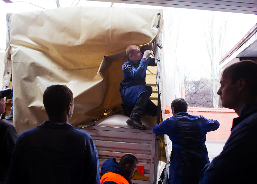 A mine worker works to open a truck of a humanitarian aid convoy from Russia at Zasyadtko Mine on March 7, 2015 in Donetsk, Ukraine.