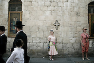 Jewish Orhodox walk past Christian icons in the Armenian Quarter in Jerusalem's Old City on april 3, 2010