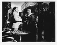 10..Maghrebi women, wearing hijab headscarves, gossip in front of a Belleville café.