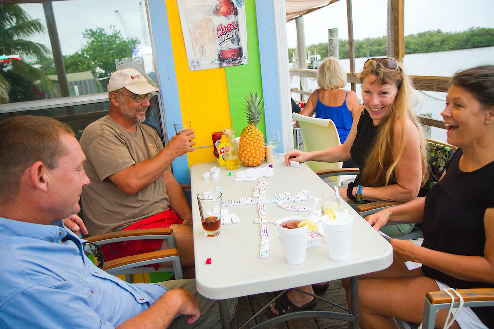 "(L-R)Matt Thompson, Pat Olkowski, Nancy Thompson and Becky Cole play domino's at Bert's Bark & Grill. Matlacha (pronounced ""MAT-la-shay"") is located just west of Ft. Myers and Cape Coral on Pine Island in Lee County and is a mix of Key West meets Old Florida fishing village. ""We're a quaint little drinking village with a fishing problem,"" laughs a local who goes by the name Bear..Photos by James and Julie Branaman"