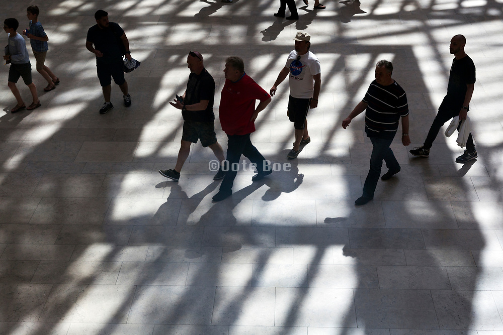 people walking on a floor with ceiling shadow at the Rijksmuseum in Amsterdam
