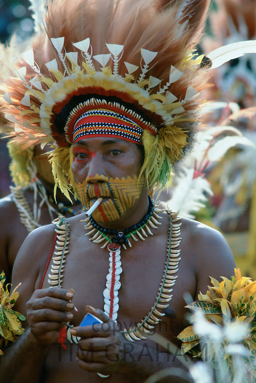 Tribesman smoking a cigarette and with face paint and feathered headdress at a tribal gathering at Mount Hagen in Papua New Guinea