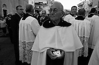 Un parroco che attende la statua della Santa protettrice del paese. La foto è stata scattata durante la processione della Madonna del Carmine il 15-07-2010 a Mesagne (Br).