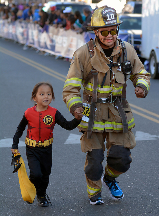 gbs101616v/SPORTS -- Navajo Nation firefighter Jeremy Curley of Window Rock, AZ, in his bunker gear, finishes the half marathon with his son Chasen, 6, during the Duke City Marathon on Sunday, October 16, 2016. (Greg Sorber/Albuquerque Journal)