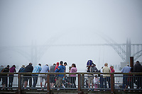 People stand on a pier at the Newport, Oregon harbor looking down at resting California Sea Lions and out at the Yaquina Bridge.