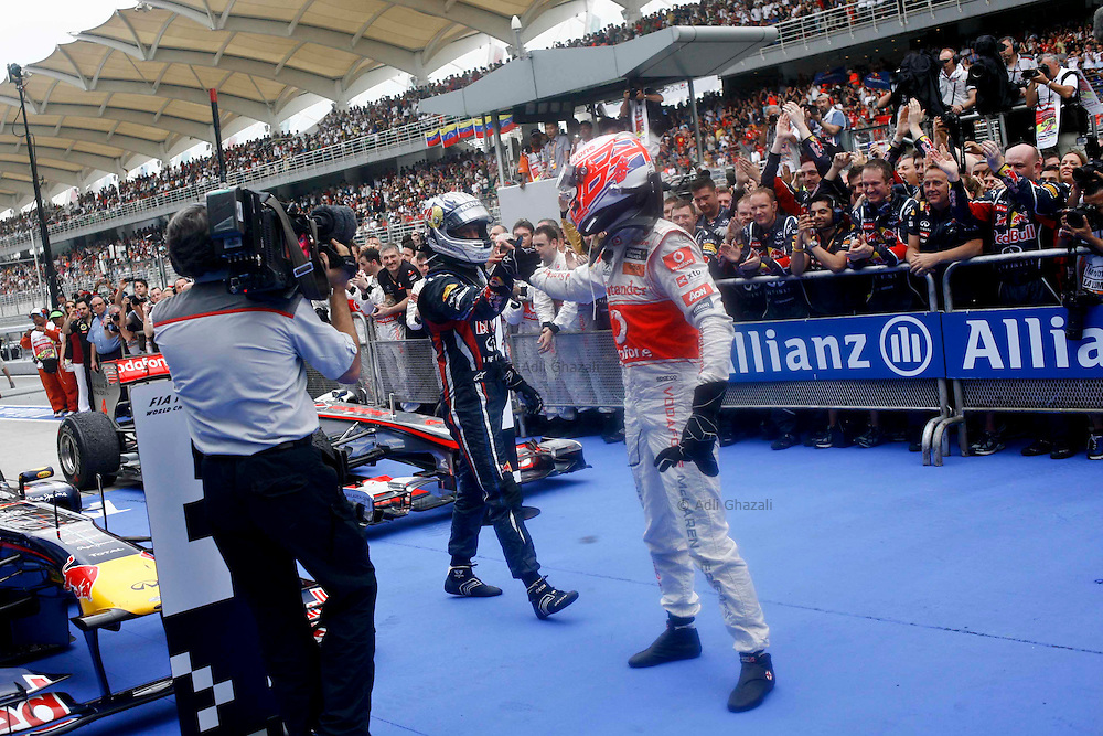 Sebastian Vettel of Germany and Red Bull Racing celebrates with Jenson Button of Mercedes Mclaren on 2nd place in parc ferme after winning the Malaysian Formula One Grand Prix at the Sepang Circuit on April 10, 2011 in Kuala Lumpur, Malaysia.