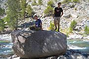 Two teenage boys atop famous John Muir Rock, along the John Muir Trail. Along Evolution Creek, Sequoia-Kings Canyon WIlderness; Kings Canyon National Park, California, USA.